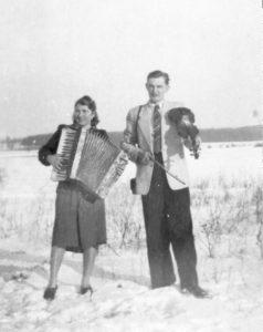 Eine junge Frau mit Akkordeon und ein junger Man mit einer Geige in Pommern 1952